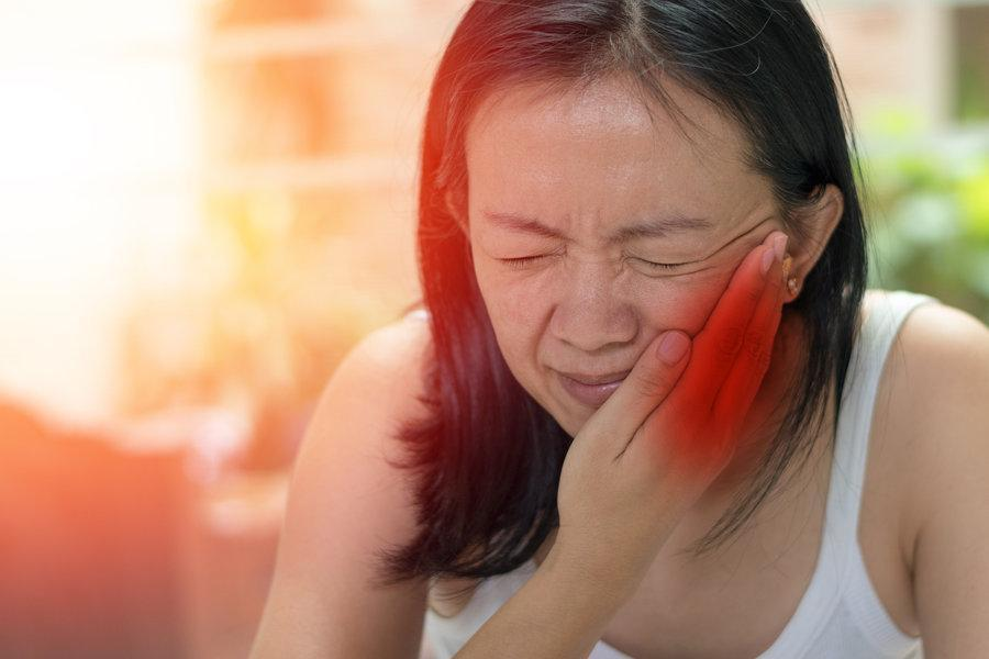 Woman holding jaw from pain | Dental Emergency Care Los Gatos