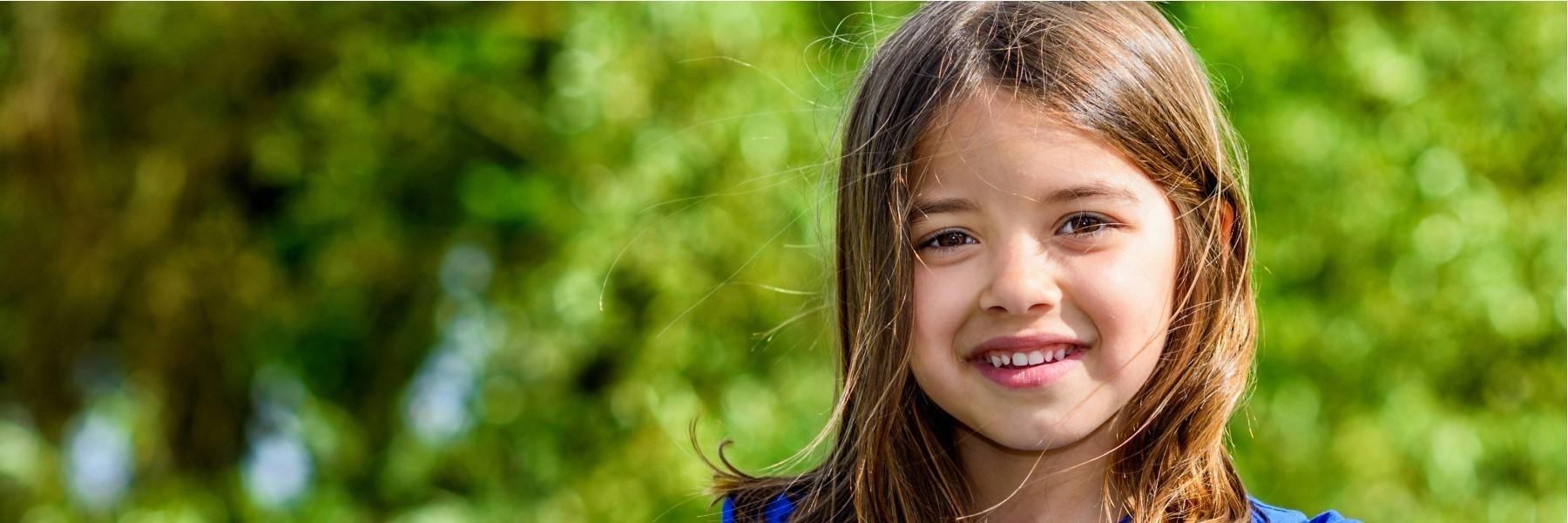 Little Girl Smiling with tree in background | Children's dentistry los gatos ca